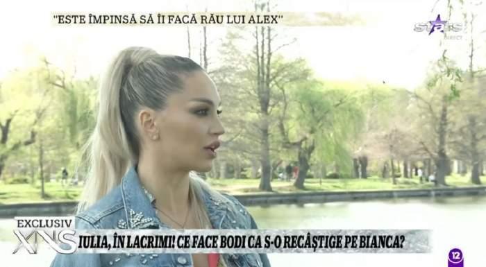 Iulia Sălăgean dă un interviu pentru Xtra Night Show. Blonda poartă o geacă de blugi.