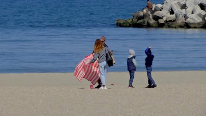 o femeie cu doi copii pe plaja