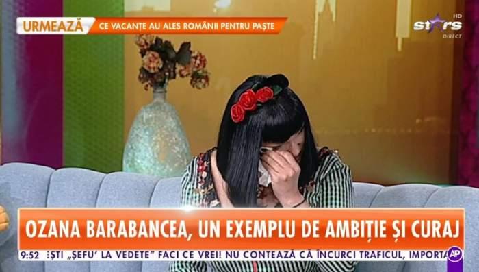 Ozana Barabancea poartă o rochie în dungi albe și negre. Artista are pe cap o coroniță roșie cu flori și își șterge lacrimile cu un șervețel.