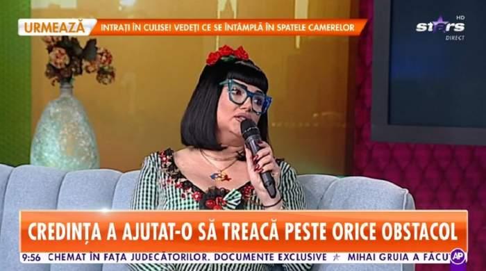 Ozana Barabancea poartă o rochie în dungi albe și negre și o coroniță cu flori roșii pe cap. Vedeta vorbește la microfon, la Antena Stars.
