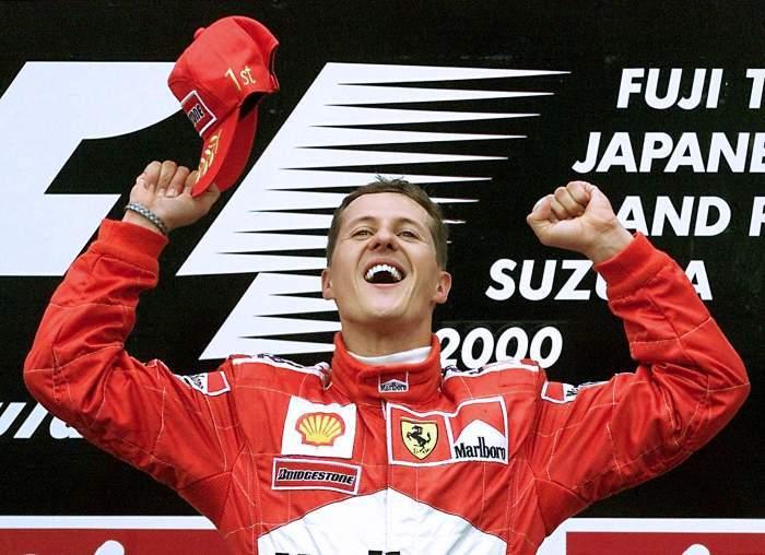 Michael Schumacher, îmbrăcat în roșu, bucurându-se