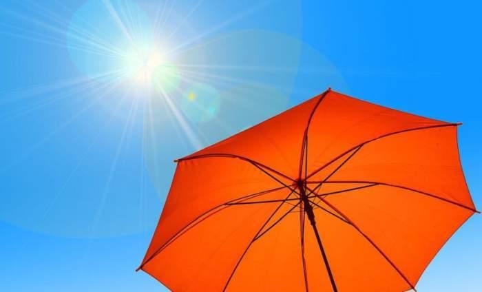 Un cer senin cu soare și o umbrelă portocalie