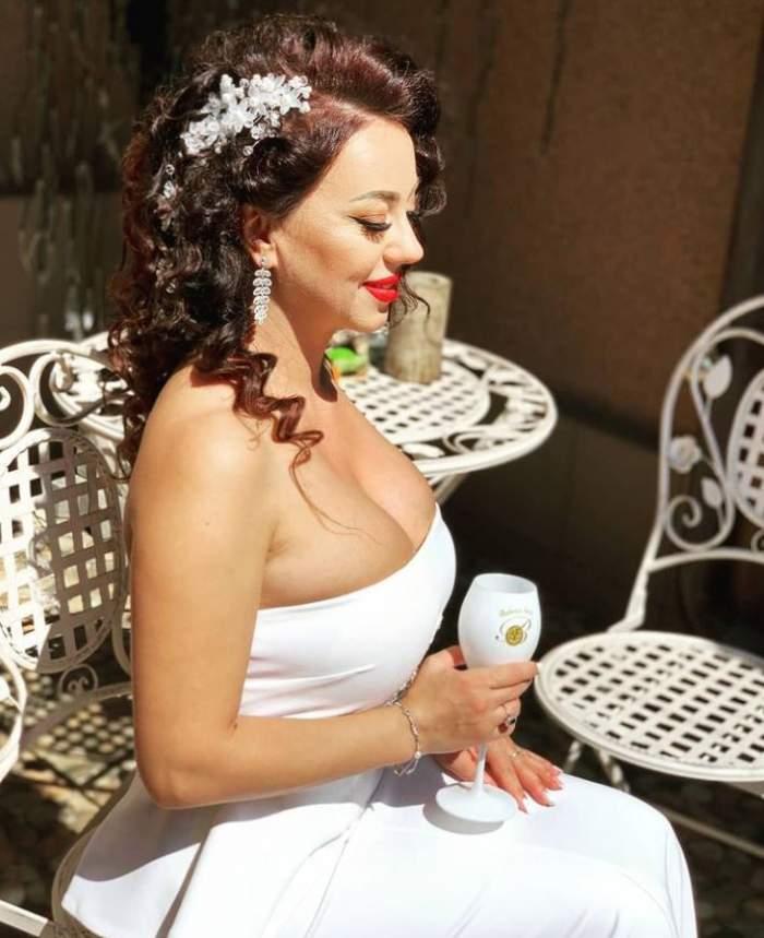 Larisa Dragulescu este in rochie de mireasa, sta pe un scaun si are un pahar in mana