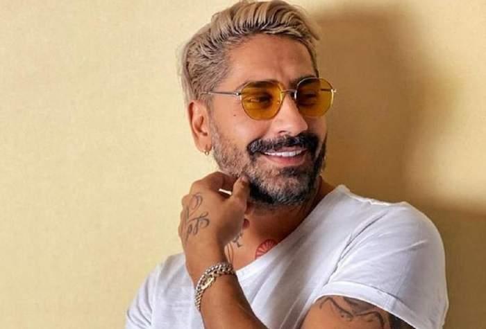 Connect-R poartă ochelari de soare oranj. Cântărețul e îmbrăcat cu un tricou alb și zâmbește larg, având o mână la nivelul bărbiei.