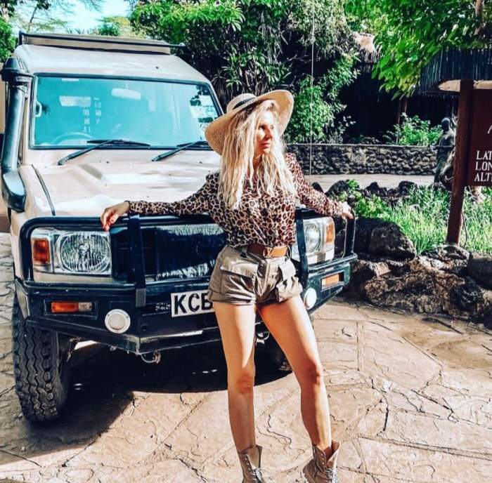 Andreea Banica este imbracata de safari si se sprijina de o masina de teren