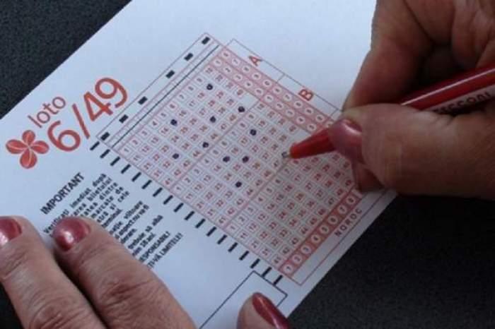 O femeie cu unghii colorate, bifează numerele câștigătoare la Loto