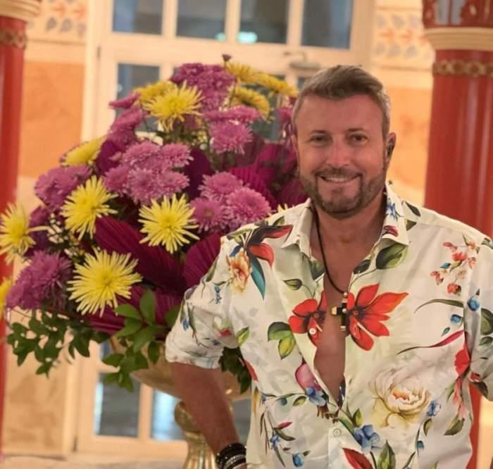 Catalin Bitezatu are o camasa cu flori si in spate o vaza cu flori colorate