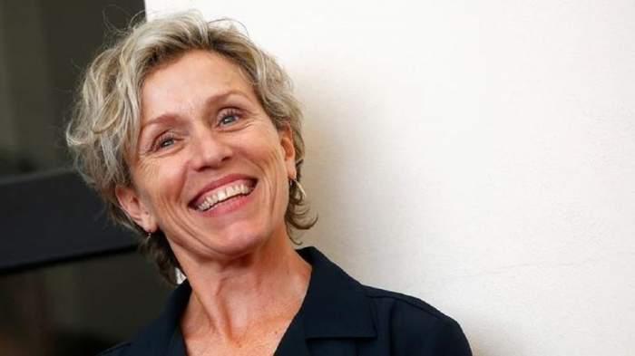 Frances McDormand poartă un sacou negru. Artista zâmbește larg.