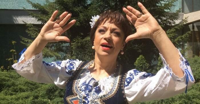 Adriana Trandafir e îmbrăcată cu o ie albă cu model albastru și o vestă neagră. Vedeta are în păr o floare albă și ține mâinile în aer.