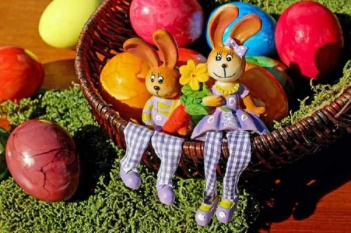 Un coș cu ouă colorate și două jucării în formă de iepurași