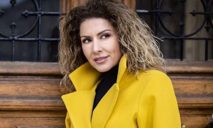 Carmen Brumă poartă un palton galben, iar pe dedesubt o bluză neagră. Vedeta zâmbește și privește într-o parte.
