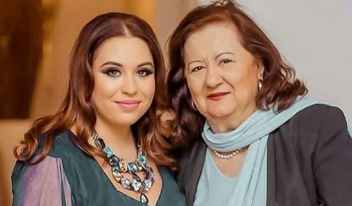 Oana Roman și Mioara Roman stau una lângă cealaltă. Oana Roman poartă o rochie turcoaz, iar mama ei o bluză bleu și un sacou negru.
