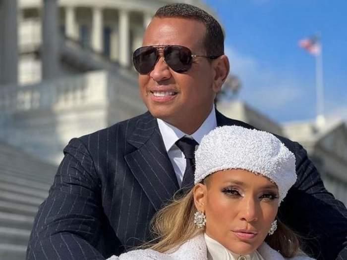 Alex Rodriguez și Jennifer Lopez sunt pe niște scări. El poartă cămașă albă, ochelari de soare și sacou negru, iar ea o beretă albă și o haină în aceeași nuanță.