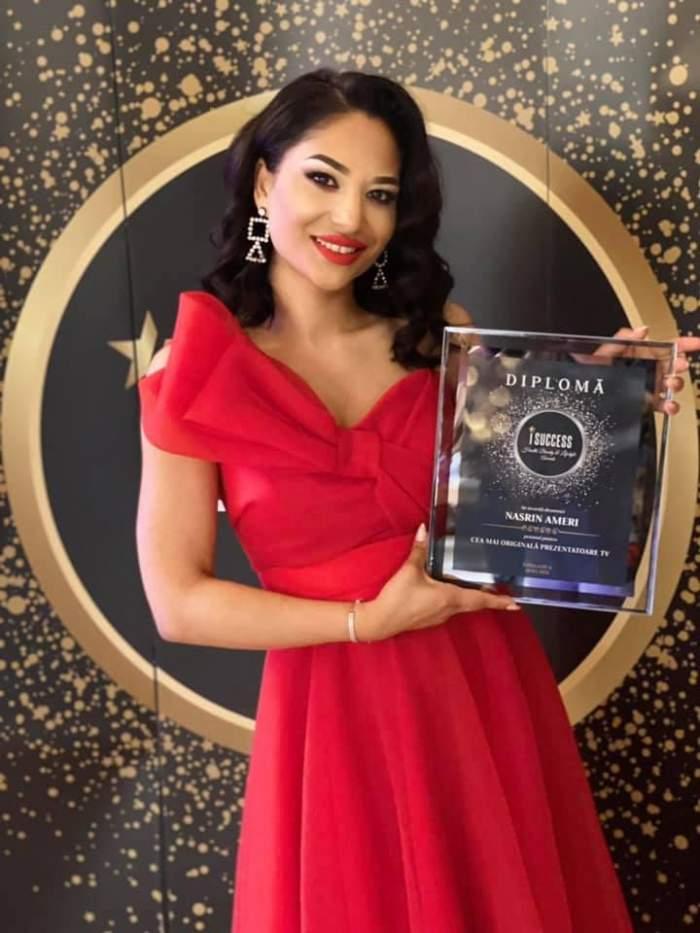 Nasrin în rochie roșie, cu premiul în brațe.