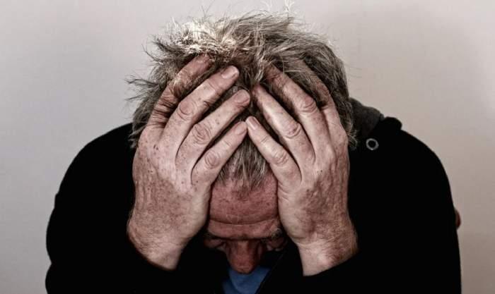 Un bărbat îmbrăcat în hanorac negru. Acesta privește în jos și-și ține capul în palme.