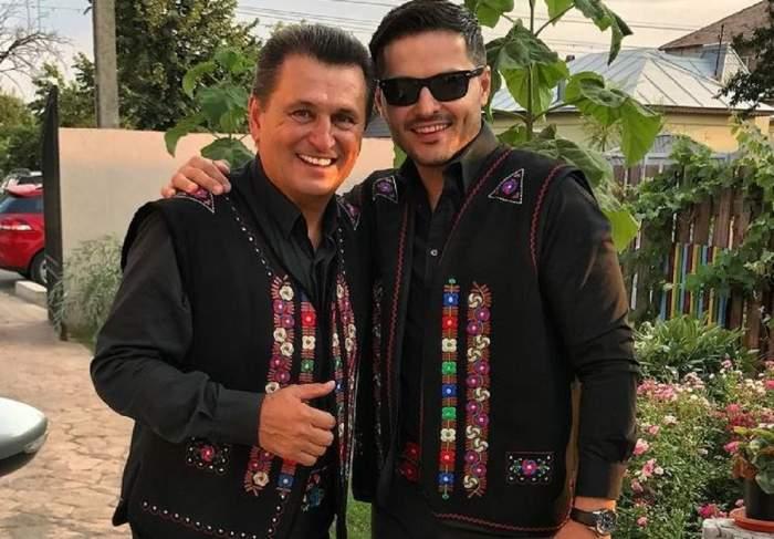 Liviu Vârciu și Nea Mărin se află în curtea casei. Amândoi poartă haine tradiționale negre, cu imprimeuri colorate, și zâmbesc larg.
