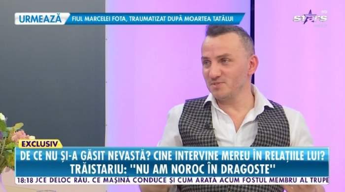 Mihai Trăistariu poartă o cămășă albă și o vestă în pătrățele alb-negru pe deasupra. Artistul dă un interviu pentru Antena Stars.