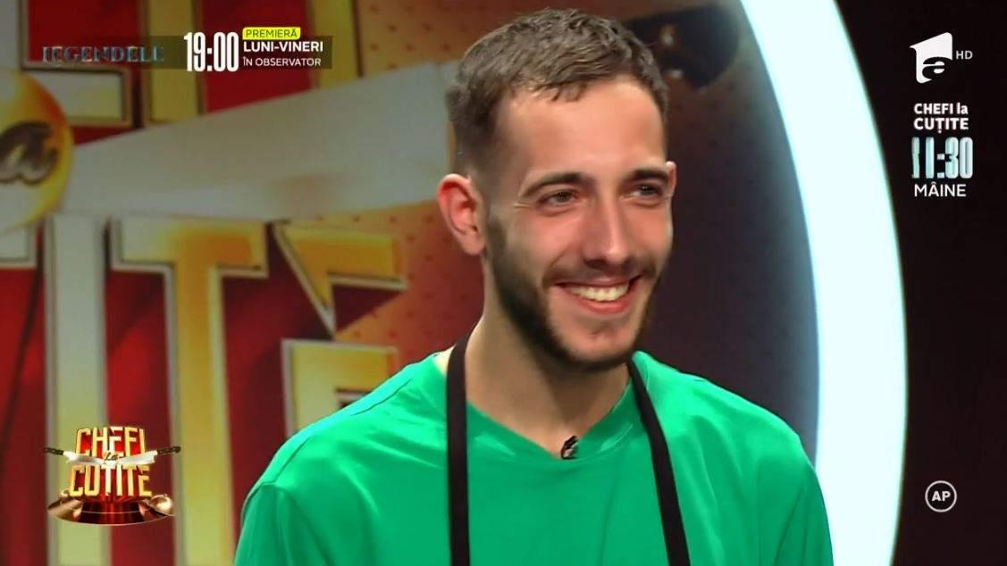 Luca Pintea este la Chefi la cuțite. Concurentul poartă tricou verde și șorț negru. Tânărul zâmbește larg.