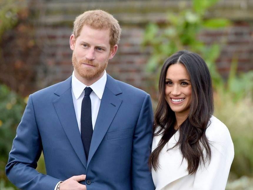Harry și Meghan Markle, la braț, îmbrăcați elegant și zâmbitori