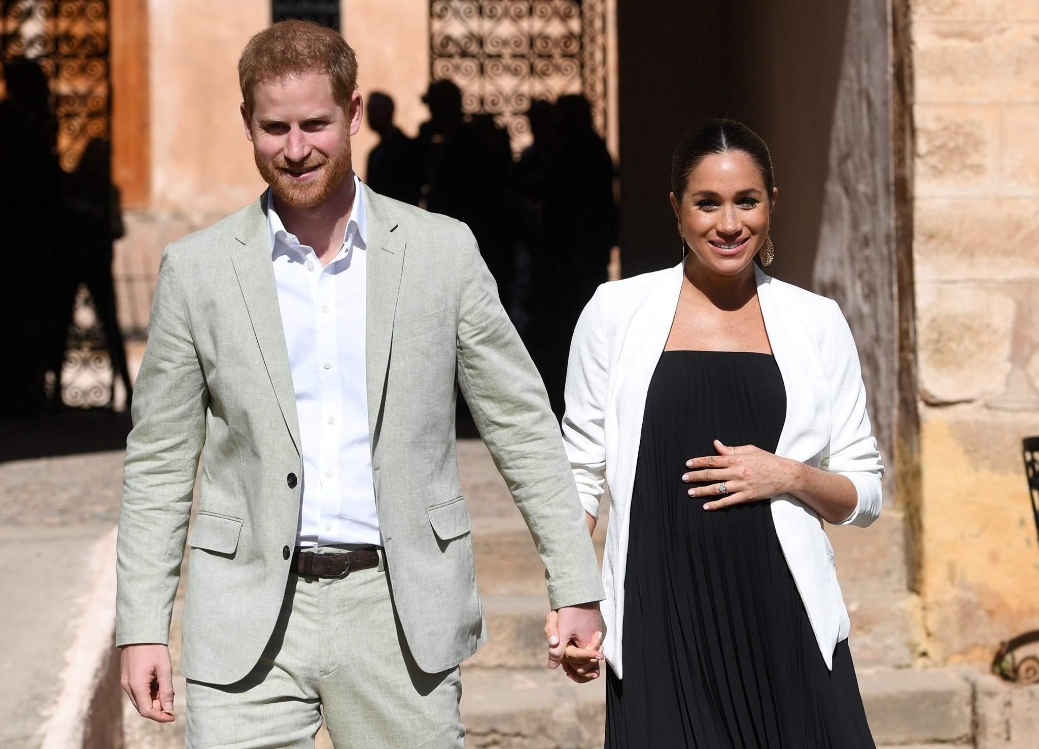 Meghan Markle cu mâna pe burtă, ținându-l pe Harry lângă ea, îmbrăcat la costum gri