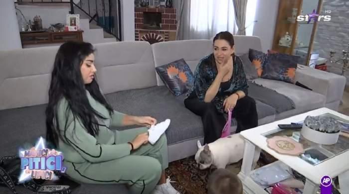 Elena Ionescu și Oana Roman stau pe o canapea gri. Artista poartă un trening verde și ține un adidas alb în mână, iar fosta soție a lui Marius Elisei e îmbrăcată în negru și zâmbește.
