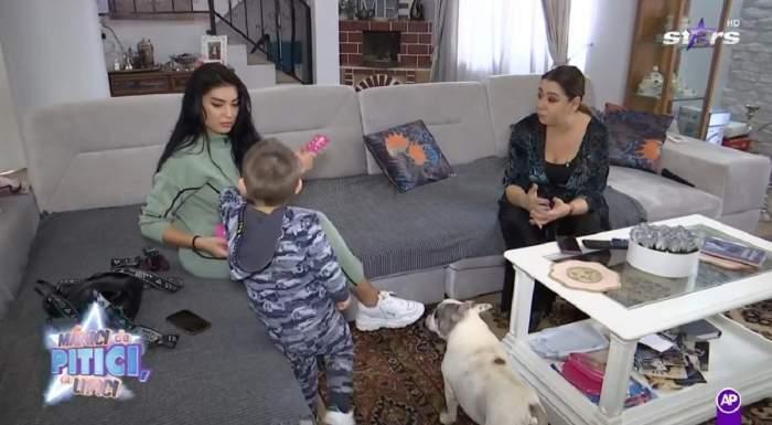 Elena Ionescu și Oana Roman stau pe o canapea gri. Artista poartă un trening verde și ține un adidas alb în mână, iar fosta soție a lui Marius Elisei e îmbrăcată în negru. Cântăreața vorbește cu fiul ei.