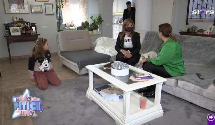 Oana Roman stă pe canapea. Vedeta poartă o bluză verde și pantaloni negre. Aceasta discută cu specialistul în parenting. Marius Elisei stă în picioare și fiica lor pe covor.