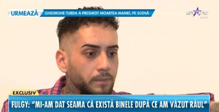 Fulgy de la Clejani dă un interviu pentru Antena Stars. Artistul poartă o cămașă în pătrățele albastre și roșii.