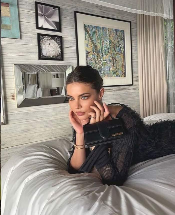Cristina Ich sta pe pat, are o rochie neagra si o geanta mica in mana, se uita inainte