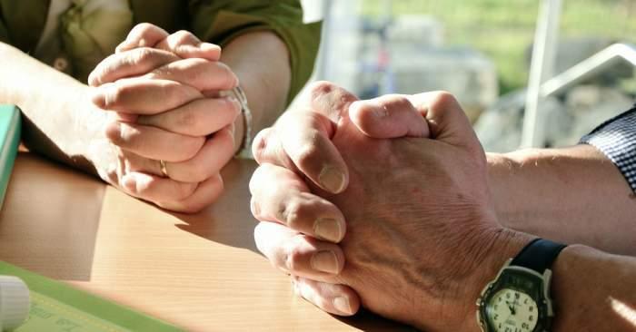 Imagine cu doua persoane care isi tin mainile incrucisate sa se roage