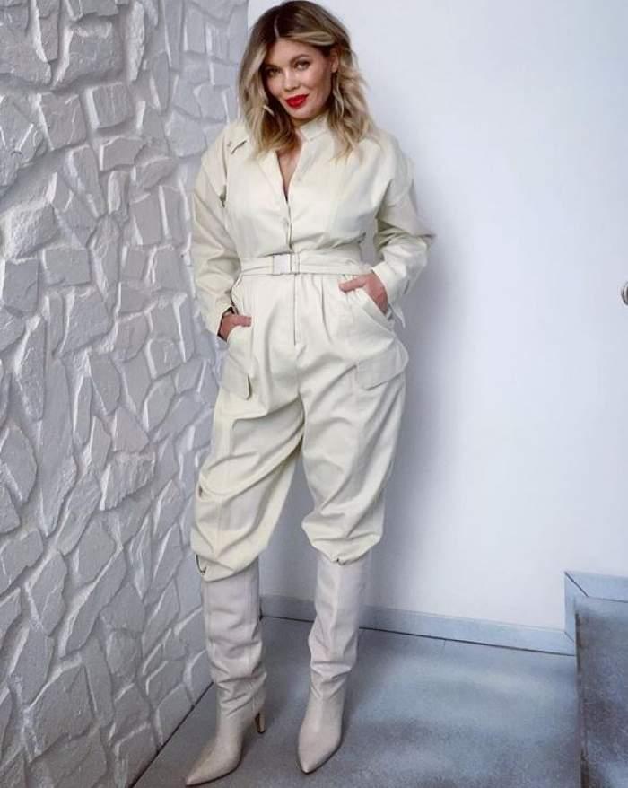 Gina Pistol poartă o salopetă albă și cizme albe. Vedeta își ține mâinile în buzunare.