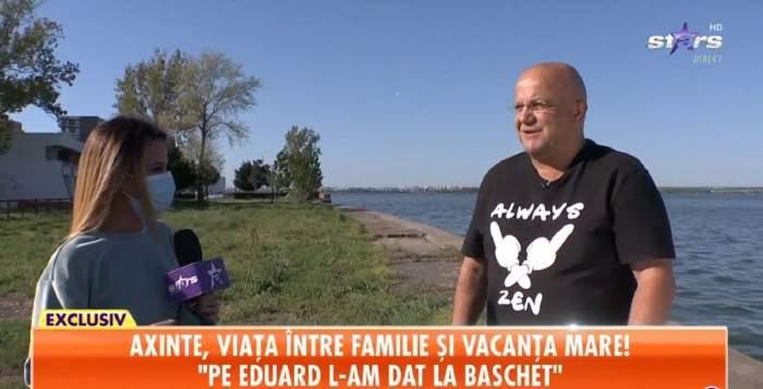 Axinte dă un interviu pentru Antena Stars. Actorul se află afară, în fața mării, și poartă un tricou negru cu scris și desene albe.