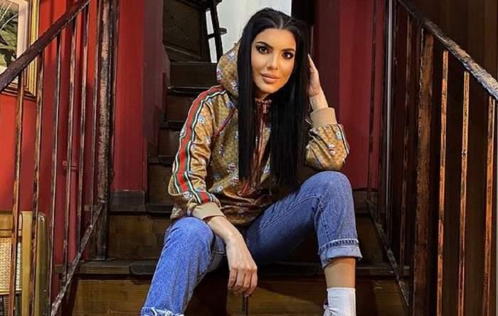 Andreea Tonciu stă pe niște scări din lemn. Vedeta poartă blugi și un hanorac maroniu, de firmă. Bruneta își ține o mână prin păr și cotul sprijinit pe genunchi.