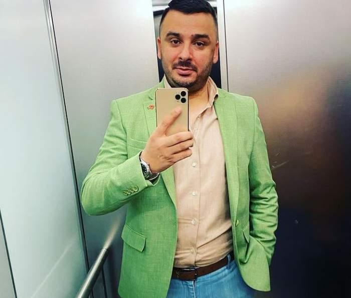Liviu Guță e în lift. Artistul poartă cămașă crem, sacou verde și blugi albaștri.