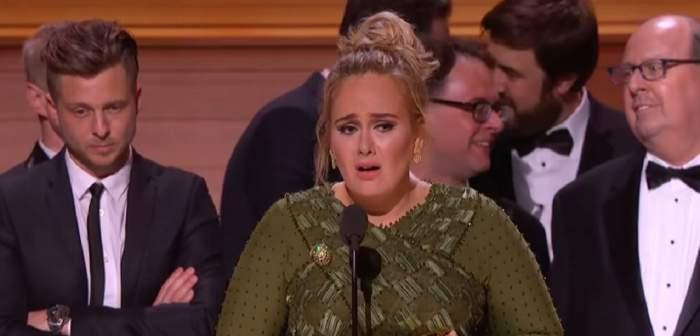 Adele la premiile Grammy. Vedeta ține un discurs în lacrimi și poartă o rochie verde. În spatele ei sunt mai mulți bărbați.