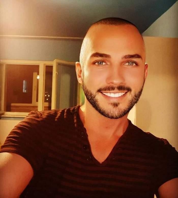 Mihai Trăistariu își face un selfie. Cântărețul poartă un tricou negru și zâmbește larg.