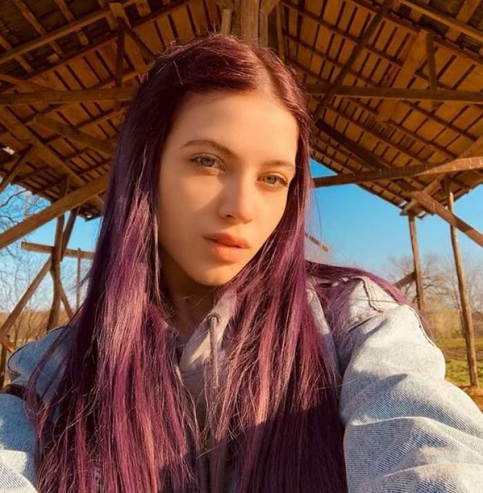 Roxen poartă un hanorac gri. Vedeta își face un selfie afară. În spatele ei se vede acoperișul unei case din lemn.
