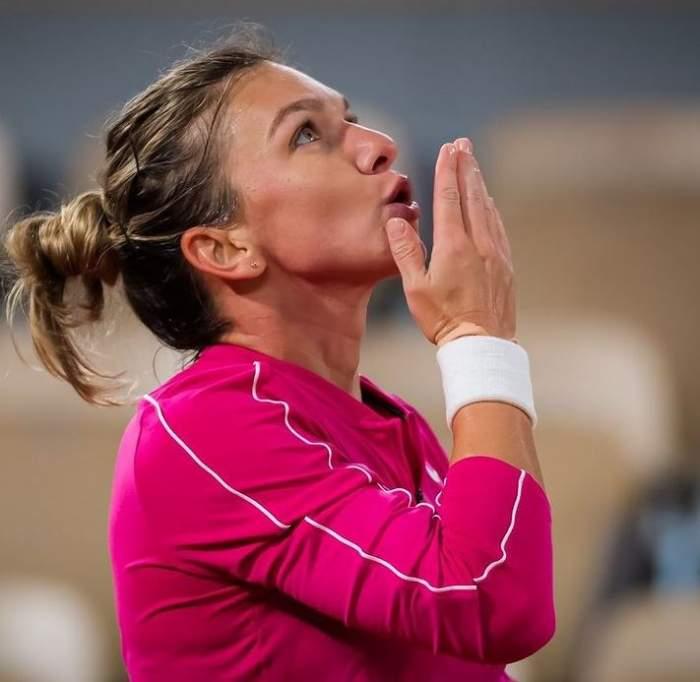 Simona Halep e la un meci de tenis. Sportiva poartă o bluză roz de trening și privește în sus, având buzele țuguiate și mâna în dreptul gurii.