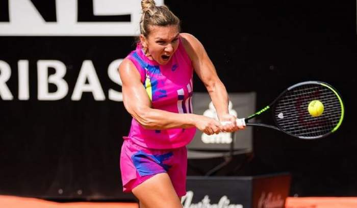 Simona Halep e la un meci de tenis. Sportiva poartă un echipament roz, format din maiou și pantaloni scurți.