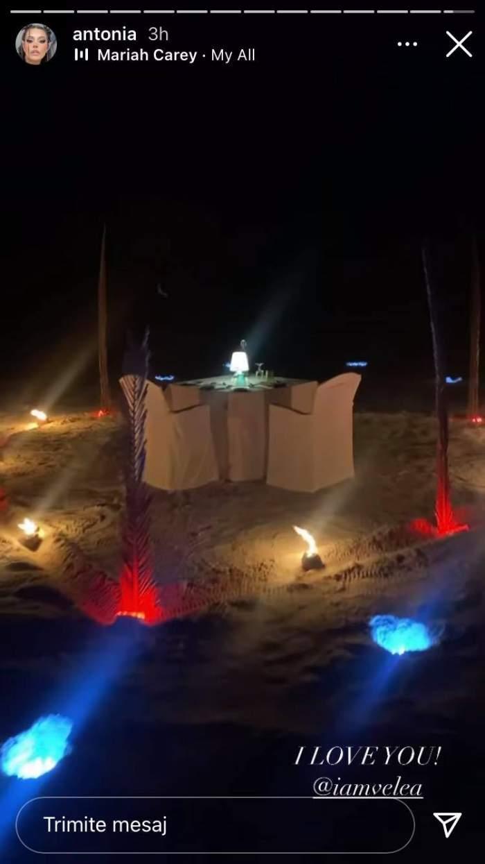Antonia i-a pregătit o cină romantică lui Alex Velea, pe plajă. În imagine sunt două scaune și o masă albă, toate înconjurată de lumini roșii și albastre.