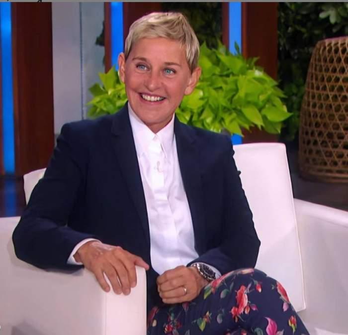 Ellen DeGeneres este pe fotoliu in emisiunea ei, zambeste, are sacou negru si camasa alba