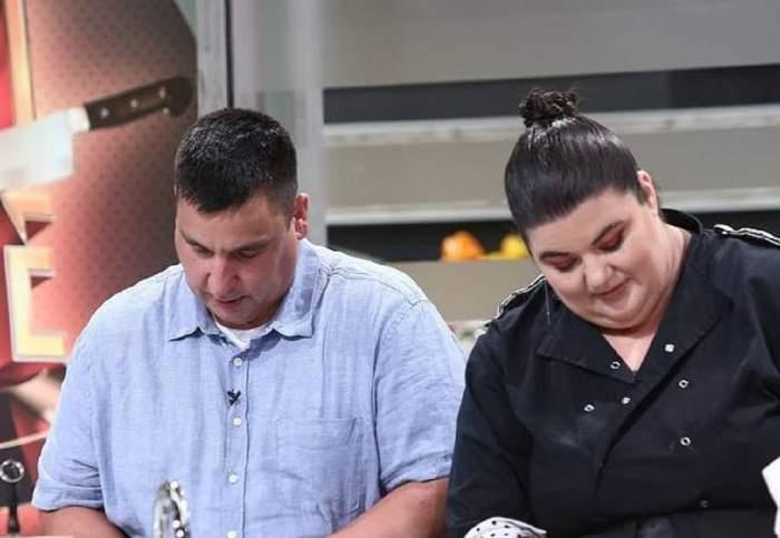 Claudia Radu și iubitul ei gătesc împreună la Chefi la cuțite. Ea poartă o uniformă neagră de bucătar, iar el o cămașă bleu cu mânecă scurtă.