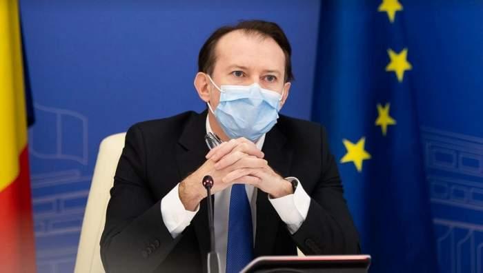 Florin Cîțu e la o conferință de presă. Premierul poartă mască de protecție și costum negru.