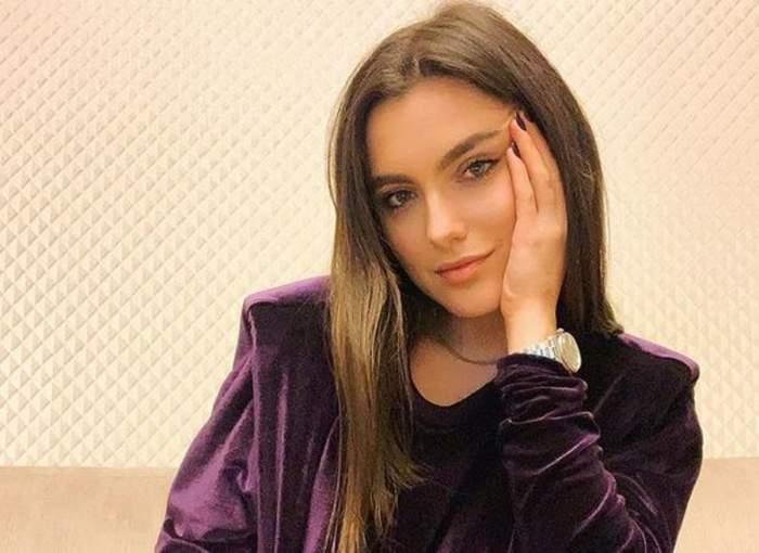 Alexia Eram poartă un trening mov. Artista își ține o palmă pe obraz.