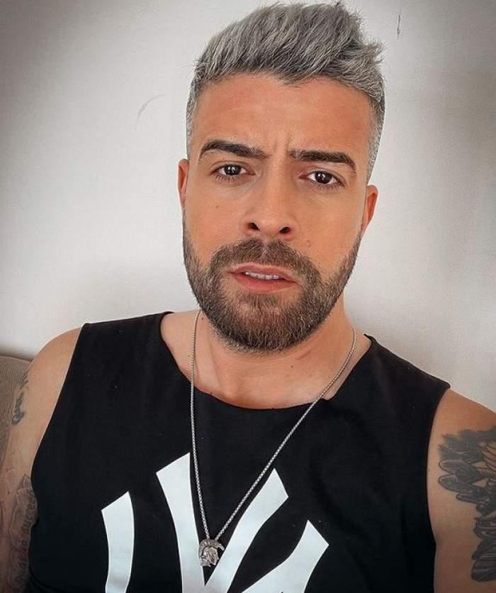 Speak poartă un maiou negru cu model alb. Artistul își face un selfie.