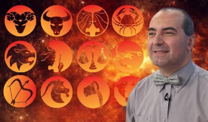 Astrologul Remus Ionescu poartă o cămașă și un papion gri. Lângă el sunt simboluri cu toate zodiile.