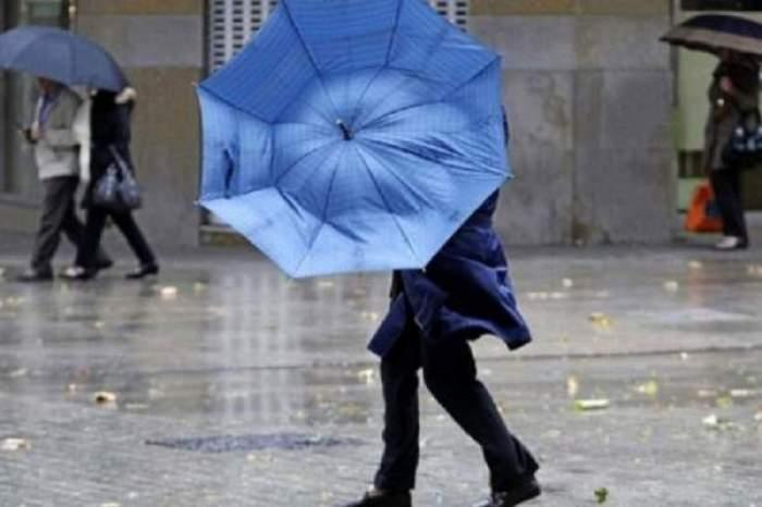 o femeie cu umbrela in ploaie