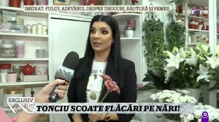 Andreea Tonciu dă un interviu la Xtra Night Show din florărie. Vedeta poartă un tricou alb și pe deasupra sacou negru.