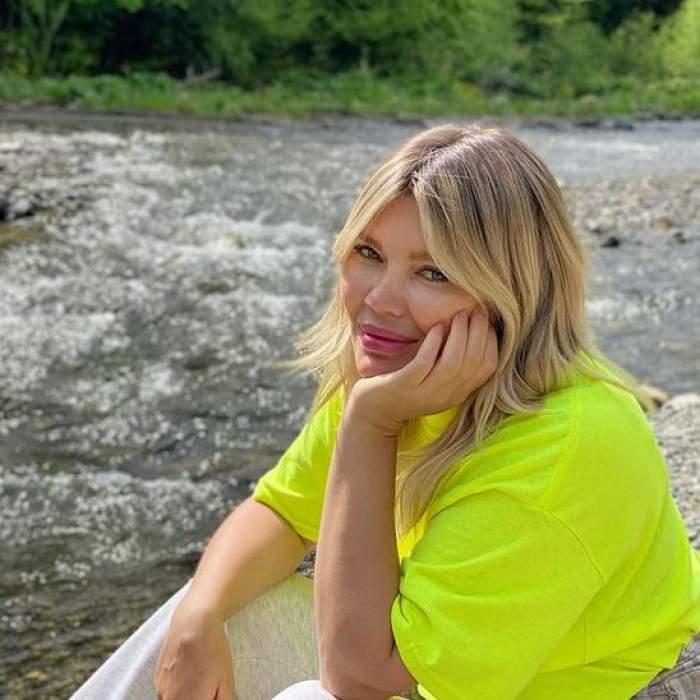 Gina Pistol e pe marginea unui lac și poartă un tricou galben cu nuanțe de neon.