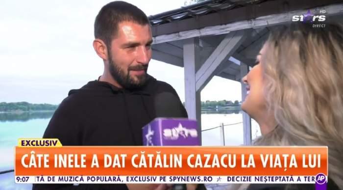 Cătălin Cazacu dă un interviu pentru Antena Stars și poartă un tricou negru. În spatele lui se vede un lac.